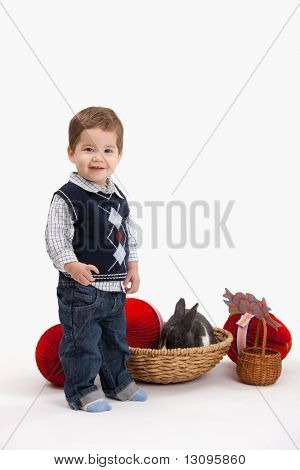 Happy little boy with Easter bunny and decoration, looking at camera, isolated on white background.