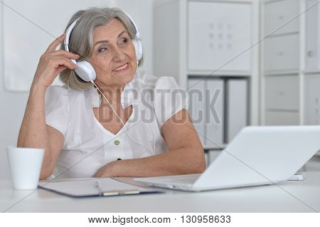 Portrait of a senior woman with headphones and laptop