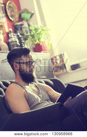 Male model sitting on a couch in a living room reading a book