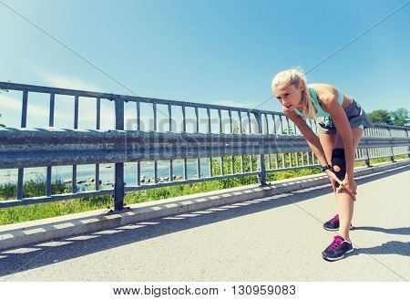 fitness, sport, exercising and healthy lifestyle concept - young woman with knee support brace injured leg outdoors