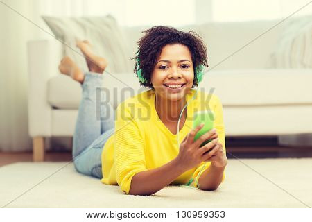 people, technology and leisure concept - happy african american young woman lying on floor with smartphone and headphones listening to music at home