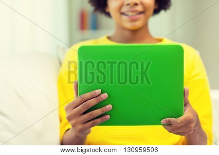 people, technology and leisure concept - close up of happy african american young woman sitting on sofa with tablet pc computer at home