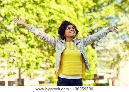people, race, ethnicity and portrait concept - happy african american young woman with open arms in summer park