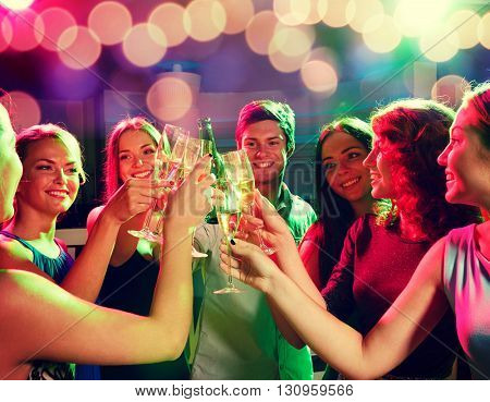 party, holidays, celebration, nightlife and people concept - smiling friends clinking glasses of champagne and beer in club