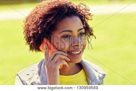people, technology and leisure concept - happy african american young woman calling on smartphone outdoors