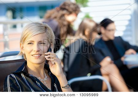 Young businesswoman talking on mobile phone, outside office building.