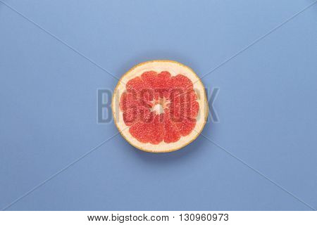 Photo kinds of pop art. Grapefruit on a blue paper texture background in the centr of photo