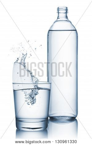 glass full of natural water with splashing and bottle