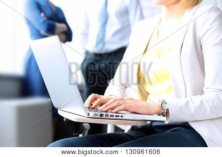 business woman working on a laptop. Collegues behind