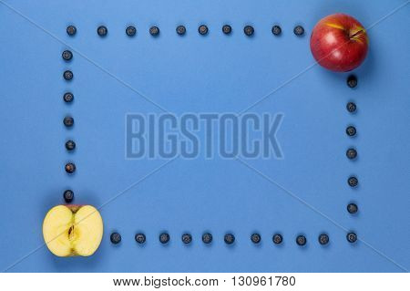 Two apples with frame of blueberries on a blue background. It can be used for advertising of healthy nutrition