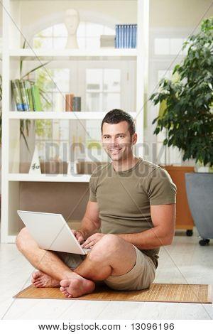Legerer Mann mit Laptop-Computer zu Hause sitzen am Boden im Wohnraum, lächelnd.