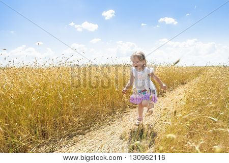 Happy two years old girl is running on farm rye field road outdoors at summer