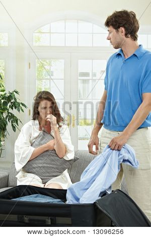 Unhappy couple breaking. Man packing his clothes into suitcase, crying woman hugging pillow in the background. Selective focus on woman.