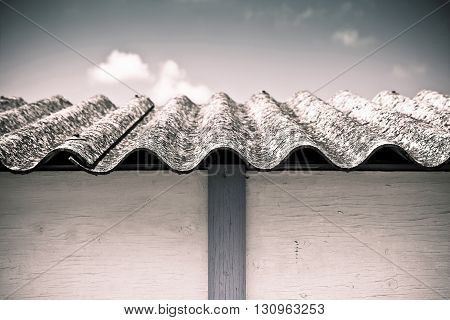 Dangerous asbestos roof - Medical studies have shown that the asbestos particles can cause cancer - toned image