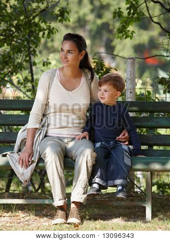 Mother and little son sitting together on bench in park, cuddling, smiling.