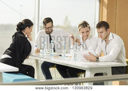 Four business people on a meeting in a conference room
