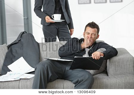 People at office. Businesswoman serving coffee to tired businessman.