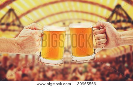 cheers two glass beer mugs in hands