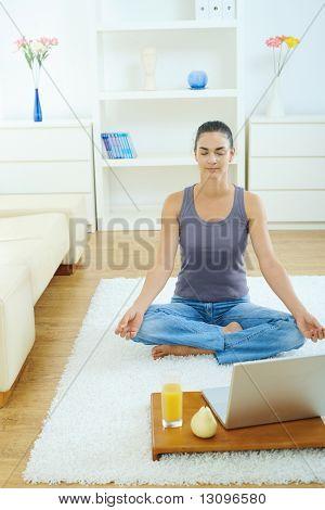 Lässig junge Frau zu Hause meditiert, sitzen im Wohnzimmer Erdgeschoss,