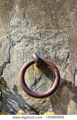 Old rusty iron ring fixed in a plaster wall - image with copy space
