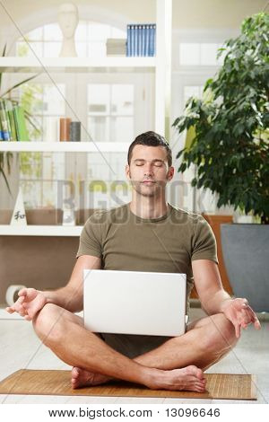Man sitting in yoga position and meditating,holding laptop computer on his knee.