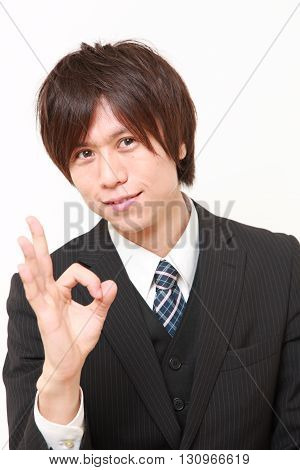 portrait of young Japanese businessman showing perfect sign on white background