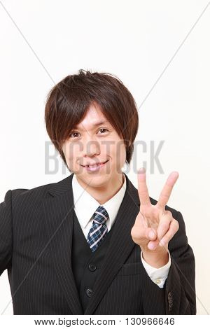 young Japanese businessman showing a victory sign