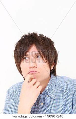 portrait of young Japanese man worries about something on white background