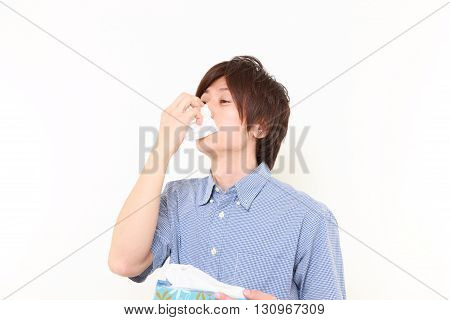 portrait of young man with a allergy sneezing into tissue on white background