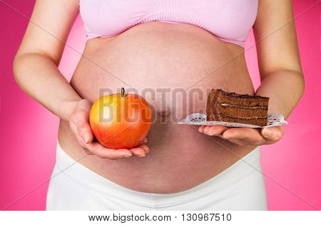 Pregnant woman holding a piece of cake and an apple on a pink background.