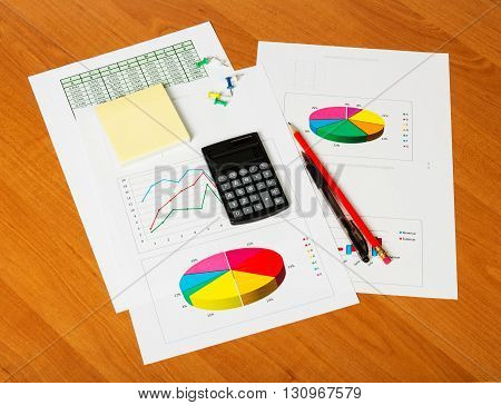 Calculator, notepad, pencil and pen on the background of the wooden desktop.