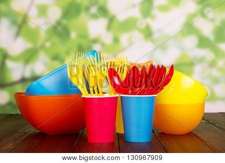 Colored plastic tableware: bowls, forks, spoons and paper cups on abstract green background.