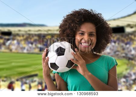 Afro woman holding a soccer ball in the stadium