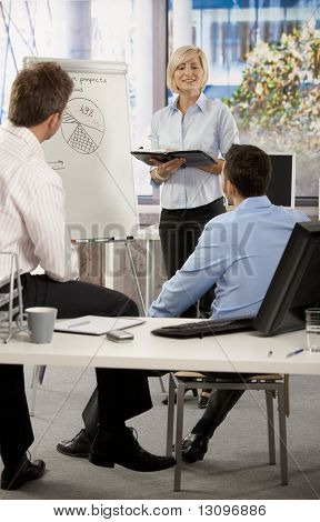 Businesspeople working together in office, Businesswoman presenting idea on whiteboard.