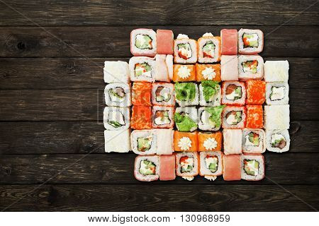 Japanese food restaurant, sushi california roll plate or platter set. Sushi at rustic wood background. Top view, flat lay with copyspace. Big party sushi set.