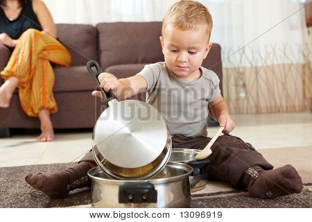 Little boy sitting on carpet in kitchen playing with cooking pots, mother sitting on sofa in background.
