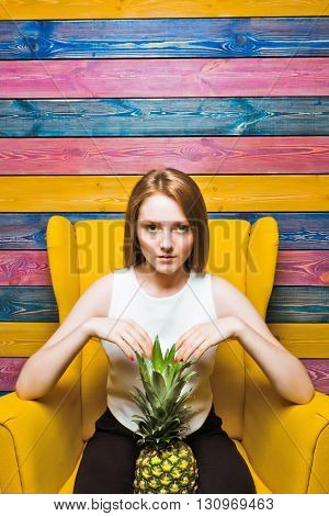 Fruit fashion girl sitting in a yellow chair. Young girl holds pineapple. Striped colorful background. Full face. Bright juicy picture
