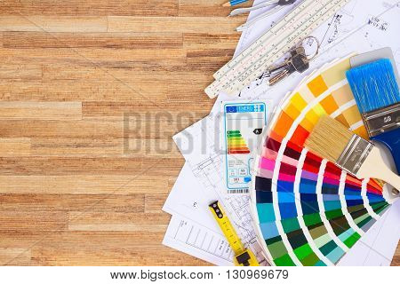 Interior designer's working table with energy rating chart, architectural plan of the house, color palette and brushes, copy space on wooden desktop
