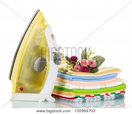 Steam iron and colored cotton towels isolated on white background.