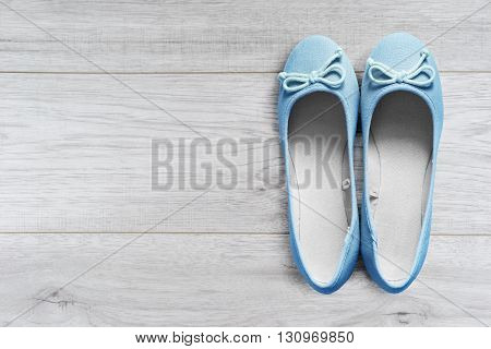 Pair of beautiful blue flat shoes on wooden floor
