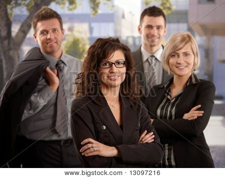 Portrait of young businesswoman standing outdoor with team smiling.
