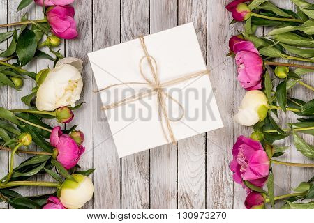 Beautiful flowers peonies with gift box on the light wooden background. Top view.