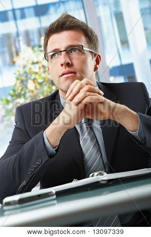 Confident businessman wearing suit and glasses looking aside with hands folded over oraniser in office.
