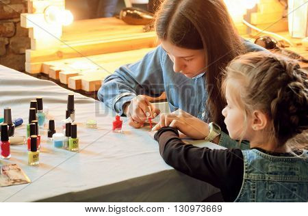 KYIV, UKRAINE - MAY 15, 2016: Unidentified little girl having manicure at the salon for kids at family friendly Street Food Festival on May 15, 2016. Kiev is the 8th most populous city in Europe.