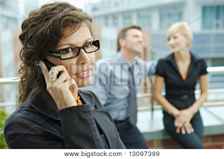 Business people talking on terrace outdoor of office building. Businesswoman in front using mobile phone.