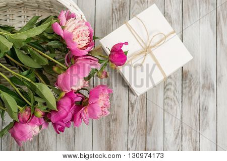 Beautiful flowers peonies in basket with gift box on the light wooden background. Top view.