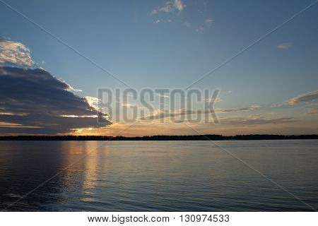 Sunset cuts through the clouds over the river Volga in Samara