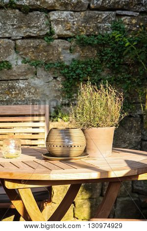 Clay pot with herbs on wooden table, stone wall background