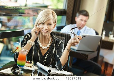 Young businesswoman sitting at table in cafe, talking on mobile phone, reading magazine.