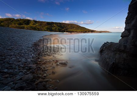 Pwll Du Bay on the Gower peninsula in South Wales, mainly covered in pebbles, used to be an extensive limestone quarry and also a popular smuggling cove.